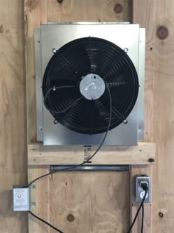 A photo of the CentricAir Attic Fan installed in an attic, with the adjustable thermostat controlling the fan.